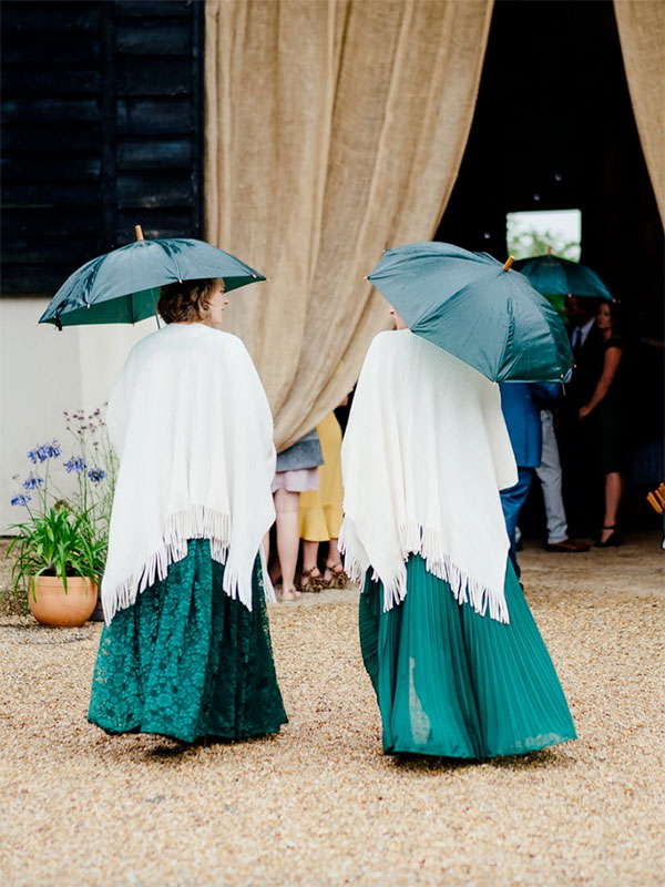 Bridesmaids with umbrellas outside the barn